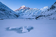 At twilight, faint stars appear as the last light of the day disappears from the tip of Mt Cook, as viewed from a frozen Hooker Lake.
