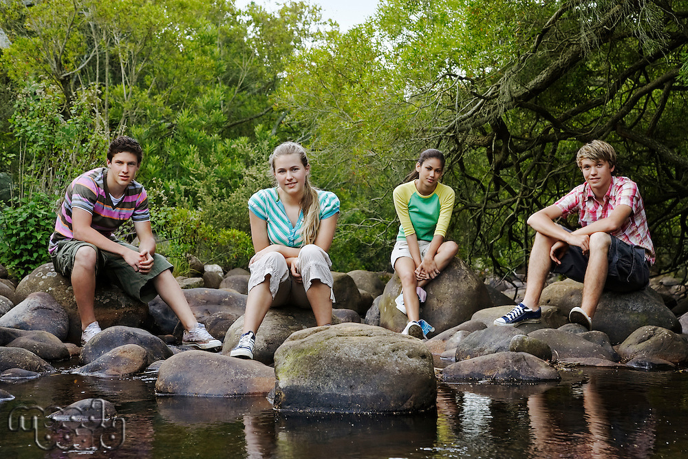 Young Friends Sitting by Creek