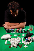 A young depressed male gambler at the gambling table gun and drugs in view model release available