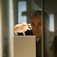 A visitor looks a figurine of a bison made of mammoth ivory during the press preview of the 'Ice Age Art - Arrival of the modern mind' exhibition at The British Museum in London. The exhibition, curated by Jill Cook, opens in London on the 7th of February and presents masterpieces of Ice Age sculpture, ceramics, drawing and personal ornaments, created over 20,000 years ago.