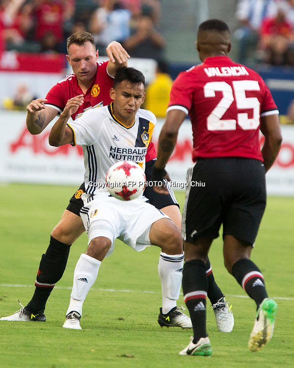 # 4 Los Angeles Galaxy midfielder , left, and Manchester United defender  battle for the ball during the first half of a national friendly soccer game at StubHub Center on July 15, 2017 in Carson, California.   AFP PHOTO / Ringo Chiu