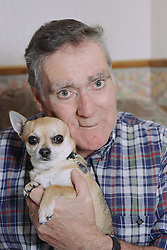 Portrait of man with Alzheimer's disease holding pet dog,