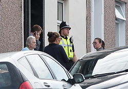 © Licensed to London News Pictures.  20/09/2017; Newport, Gwent, South Wales, UK. Police and local people stand at a house in West Street in the centre of Newport which is being searched by police, about a mile from the other property being searched in Jeffrey Street, after three people were arrested in Newport in the last 24 hours over last week's Tube attack in Parsons Green. A 25-year-old was arrested in Newport, south Wales, on Tuesday evening, and two more arrests were made this morning, 20 September. Picture credit : Simon Chapman/LNP