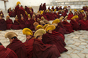 Buddhist monks of the Gelugpa school of Buddhism,wear their characteristic yellow hats, whilst waiting to debate outside the main prayer hall of Labrang Monastery.<br /> <br /> Established in 1709, Labrang housed over 4000 monks at its peak, but now only has around 1500 monks.