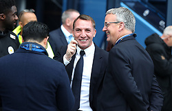 Leicester City Vice Chairman Aiyawatt Srivaddhanaprabha (back to camera) and Director of Football Jon Rudkin (right) speak to manager Brendan Rodgers during the Premier League match at the Etihad Stadium, Manchester.