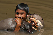 Macushi boy & Giant Otter (Pteronura brasiliensis) HABITUATED. Karanambu Otter Trust for re-introduction<br /> Savannah<br /> Rupununi<br /> GUYANA. South America<br /> RANGE: Orinoco, Amazon, and Guianas river systems<br /> IUCN: ENDANGERED SPECIES