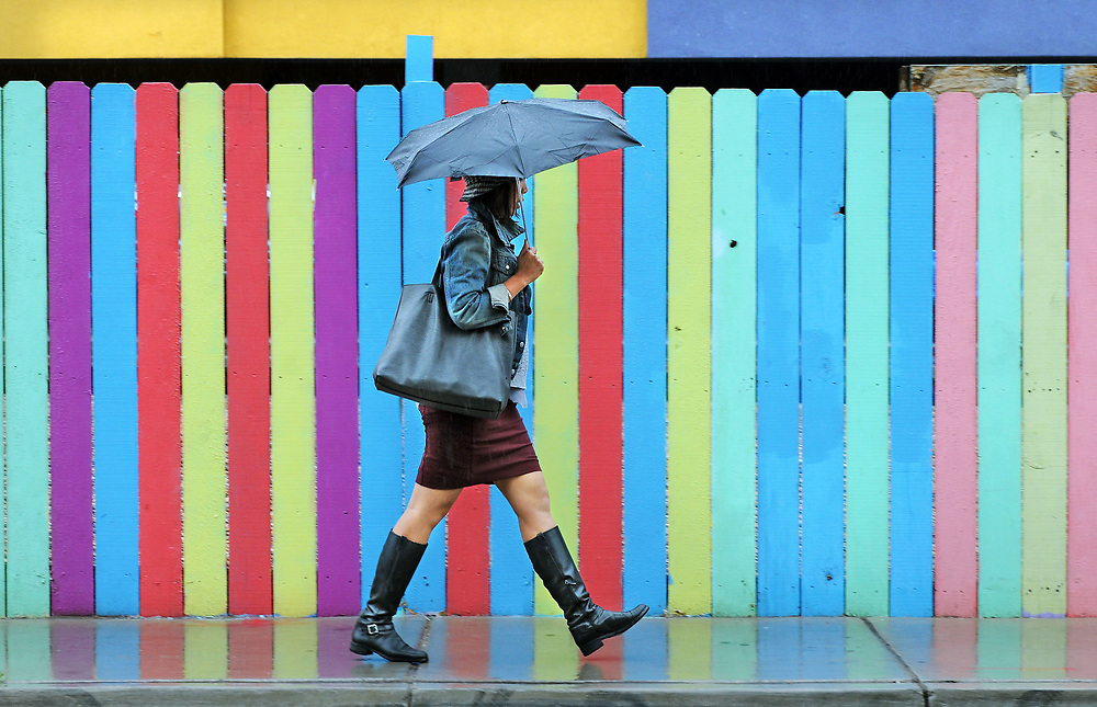 jt042517k/a sec/jim thompson/  Lorilynn Violanta walks along 2nd street and Sliver as rain hit the Albuquerque area today .Tuesday April 25, 2017. (Jim Thompson/Albuquerque Journal)