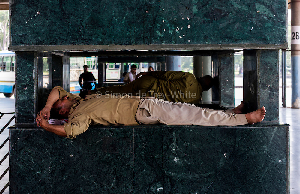 23rd September 2015, Chandigarh. Men sleep in a kiosk of the Central Bus Terminal in Chandigarh, India on the 23rd September 2015<br /> <br /> Sleeping in the outdoors is common in Asia due to a warmer climate and the fact that personal privacy for sleep is not so culturally ingrained as it is in the West. New Delhi (where most of these images were taken) is a harsh city both in climate and environment and for those working long hours, often in hard manual labour, sleep and rest is something fallen into when exhaustion overwhelms, no matter the place or circumstance. Then there are the homeless, in Delhi figures for them from Government and NGO sources vary wildly from 25,000 to more than 10 times that. Others public sleepers may simply be travellers having a siesta along the way.<br />  <br /> <br /> PHOTOGRAPH BY AND COPYRIGHT OF SIMON DE TREY-WHITE, photographer in Delhi<br /> <br /> + 91 98103 99809<br /> email: simon@simondetreywhite.com