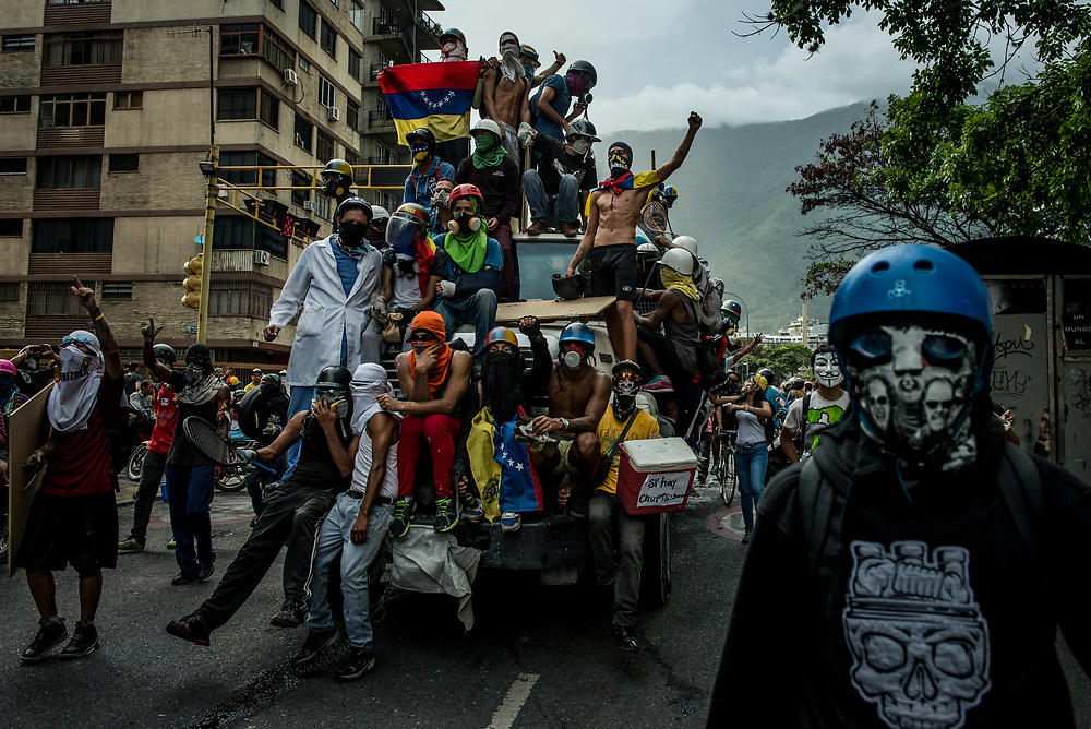 "CARACAS, VENEZUELA - MAY 22, 2017:  Anti-government protesters of ""The Resistance"" highjacked a cement truck and drove it around in celebration before popping the tires and using it as road block to prevent security forces from entering streets under their control. The streets of Caracas and other cities across Venezuela have been filled with tens of thousands of demonstrators for nearly 100 days of massive protests, held since April 1st. Protesters are enraged at the government for becoming an increasingly repressive, authoritarian regime that has delayed elections, used armed government loyalist to threaten dissidents, called for the Constitution to be re-written to favor them, jailed and tortured protesters and members of the political opposition, and whose corruption and failed economic policy has caused the current economic crisis that has led to widespread food and medicine shortages across the country.  Independent local media report nearly 100 people have been killed during protests and protest-related riots and looting.  The government currently only officially reports 75 deaths.  Over 2,000 people have been injured, and over 3,000 protesters have been detained by authorities.  PHOTO: Meridith Kohut"