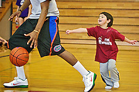 "Thomas Reed gives chase to North Idaho College basketball player Cole Luckett during a field trip to the college's gymnasium Tuesday. Reed and his fellow classmates from NIC's Childrens Center visited the basketball team for a ""scrimmage"" that evolved into the students chasing the basketball players around the gym. Earlier in the semester the children visited the basketball team and decided to come up with their own basketball team. They developed team jerseys with their own numbers, voted on colors and named themselves the Fire-Huggers."