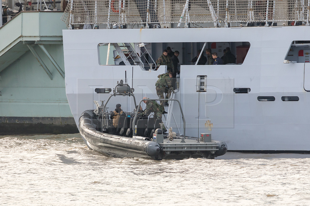 © Licensed to London News Pictures. 23/10/2018. London, UK. Dutch Royal Netherlands Marines board a RIB alongside HMS Belfast and HNLMS Zeeland during a rehearsal for a display tomorrow when the Royal Marines and Royal Netherlands Marines will stage a joint on water capability demonstration with blank ammunition. As part of the Dutch state visit, King Willem-Alexander and Queen Máxima will attend the Dutch ship HNLMS Zeeland, which is anchored next to HMS Belfast. They will join The Duke of Kent on board and will be given a 10 minute display of the Royal Marines and Royal Netherlands Marines staging a joint on water capability demonstration.Photo credit: Vickie Flores/LNP