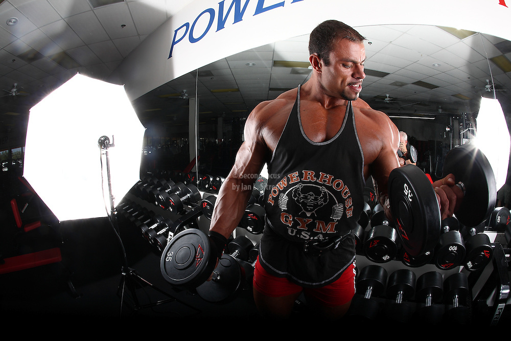 IFBB Pro Bodybuilder Daniel Hill doing dumbbell bicep curls in the gym.