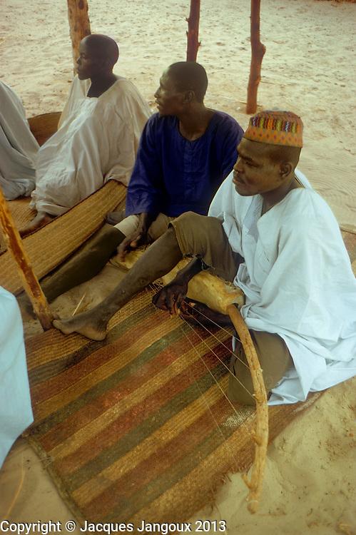 Islands of Lake Chad: Buduma man playing arched harp (bidel or biram?). The Buduma speak a language of the Afro-Asiatic family, Chadic sub-famiy.