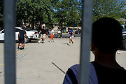 Kids play soccer in an apartment complex next to the Ivy Apartments where Thomas E. Duncan, the first confirmed Ebola virus patient in the United States, was staying with family in Dallas, Texas on October 4, 2014. Duncan is now being treated at Texas Health Presbyterian Hospital Dallas while members of his family have been isolated in the apartment. (Cooper Neill for The New York Times)