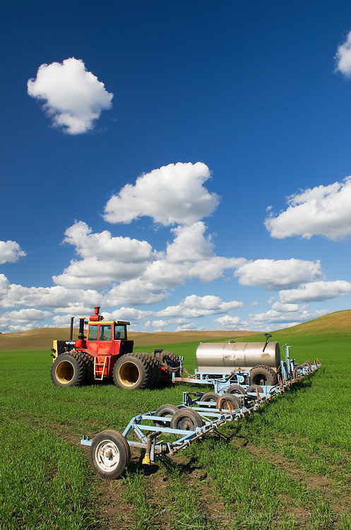 Tractor with implements in green wheat fields of the Palouse region of the Inland Empire of Washington
