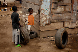 Nasu, 8 (left) and Cabrel, 8 with their wheels wait for their friends. They live in one of the poor areas which is under threat of being demolished. Yaounde, Cameroon.