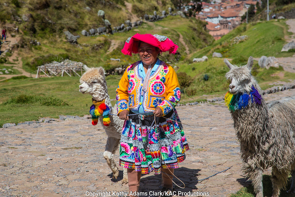 Lady in traditional dress in Cusco, Peru, with llamas. Hat denotes village or region.