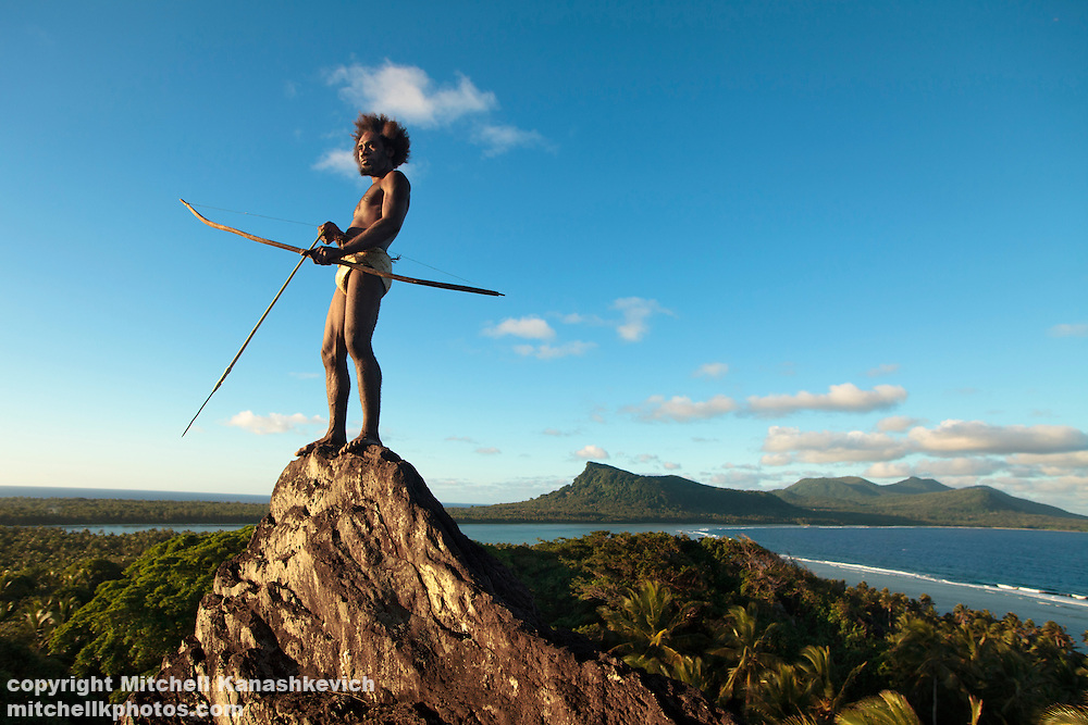 Traditional Ni Vanuatu man scans his surroundings with a bow and arrow from the Rock of Rah, Rah Lava Island, Torba Province, Vanuatu