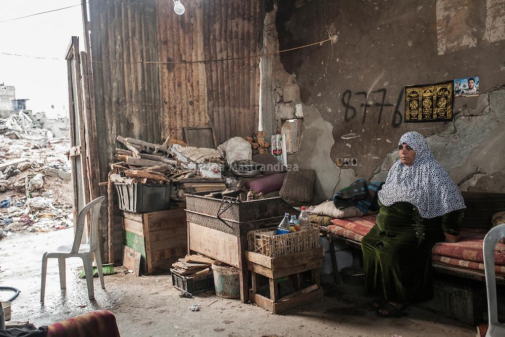 """Shejaya, quartiere a nord della striscia di Gaza. Una delle zone piu colpite dall'attacco israeliano """"Margine protettivo"""". Il quartiere è stato raso al suolo. La popolazione, a distanza di sei mesi dalla fine della guerra, vive tra le macerie della propria casa, al freddo, senza luce, gas e acqua. Nella foto una donna vive in quel che resta della sua casa distrutta e piena di macerie. Al muro le foto del figlio   morto martire."""