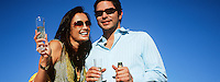 Couple celebrating with champagne outdoors, portrait
