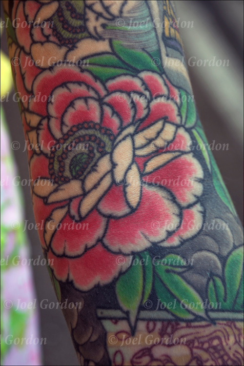 Close of small area of Japanese tattoo. <br /> <br /> Tattoos are no longer just a male thing, young women are just as likely to get a tattoo as males. <br /> <br /> Body art or tattoos has entered the mainstream it is no longer considered a weird kind of subculture.<br /> <br /> &quot;According to a 2006 Pew survey, 40% of Americans between the ages of 26 and 40 have been tattooed&quot;.
