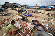 Fishing Harbour at the mouth of Cai River. Salting and drying fish.
