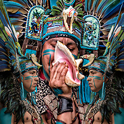 Photographic series of digital computer art from an image of profile of Aztec Dancer.<br /> <br /> Two or more layers were used to enhance, alter, manipulate the image, creating an abstract surrealistic mirrored symmetry.<br /> <br /> <br /> ___________________________________________<br /> <br /> Aztec dancer wearing his feather head dress and regalia at Drums Along the Hudson, A native American and Multicultural Celebration , in Inwood Hill Park, NYC.<br /> <br /> Members of Kalpulli Huchuetlahtolli ( K.I ) Aztec / Conchero / Mexico dance tradition to preserve and teach the dance and indigenous traditions to communities of NY and NJ. <br /> <br /> Every movement in the choreography of dance has a specific meaning. Squats and serpentine movements represent fertility, steps firmly on the ground and planting land, air and turns the spirit, advanced steps  fire and water zigzagging steps. Always relation to the four elements is found. water, fire, wind, earth.<br /> <br /> Also this number is prevalent in Mexican culture as it also represents the four directions, north, south, east, west among other interpretations. Aztec dance origins in Mexihca.