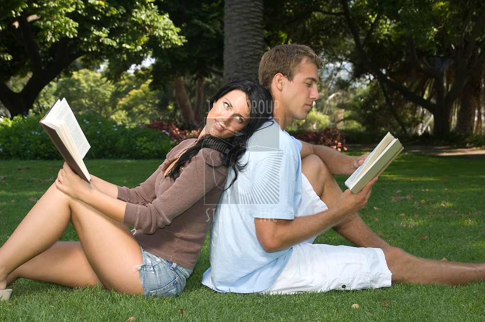 Attractive young couple sitting back to back in the park reading books