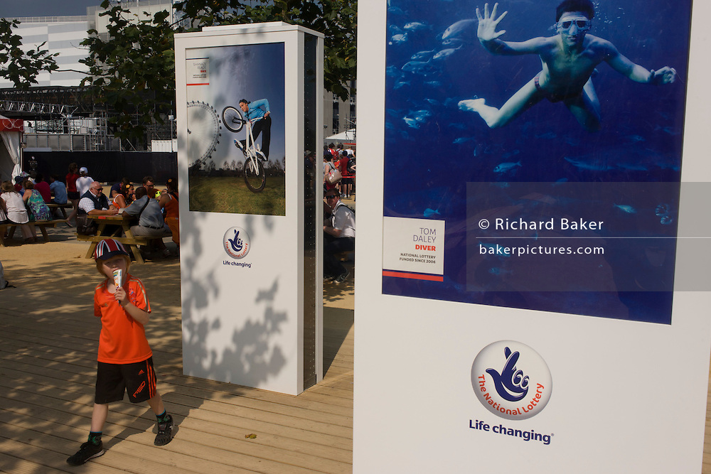 A young boy eats an ice cream below portraits of the BMX athlete Shanaze Reade and celebrated diver Tom Daley, both funded by the National Lottery, an exhibition featured in the Olympic Park during the London 2012 Olympics. As the tally for gold medals climbed, so the argument over government funding for the young gathered pace. In times of austerity, schools and sports clubs had their budgets for sport reduced and Team GB's success raised more concerns for the future of British youth as potential medal winners.