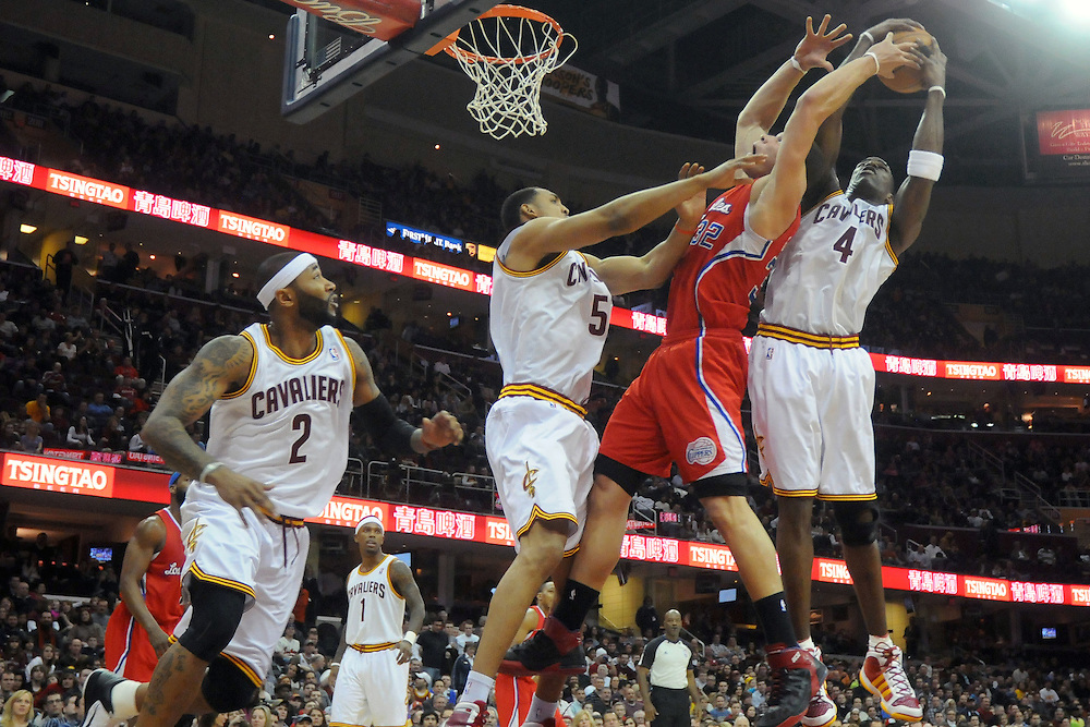 Feb. 11, 2011; Cleveland, OH, USA; Los Angeles Clippers power forward Blake Griffin (32) fights Cleveland Cavaliers center Ryan Hollins (5) and power forward Antawn Jamison (4) for a rebound during the first quarter at Quicken Loans Arena. Mandatory Credit: Jason Miller-US PRESSWIRE