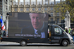 © Licensed to London News Pictures. 31/10/2019. London, UK. A mobile screen showing Boris Johnson making a promise to leave the EU on October 31st, 2019, is driven around Parliament Square in London. A general election will be held on December 12th.  Photo credit: Ben Cawthra/LNP