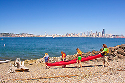 United States, Washington, Seattle. People carry a two-person sea kayak down a beach in West Seattle, across Puget Sound from downtown Seattle.