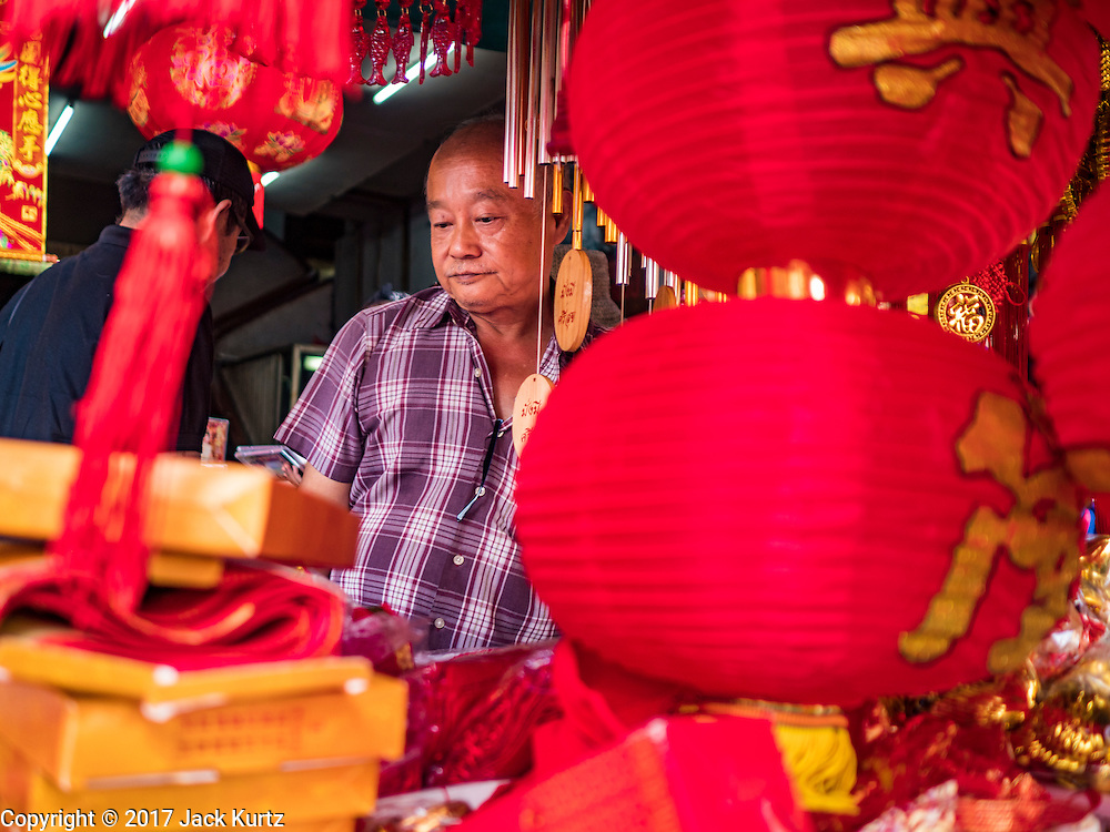 """18 JANUARY 2017 - BANGKOK, THAILAND: A vendor who sells Chinese New Year lanterns waits for customers in Bangkok's Chinatown district. Chinese New Year, also called Lunar New Year or Tet (in Vietnamese communities) starts Saturday, 28 January. The coming year will be the """"Year of the Rooster."""" Thailand has the largest overseas Chinese population in the world; about 14 percent of Thais are of Chinese ancestry and some Chinese holidays, especially Chinese New Year, are widely celebrated in Thailand.      PHOTO BY JACK KURTZ"""