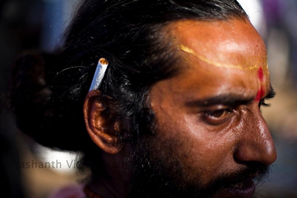 A holy man holds his ciggarete behind his ears during the Maha Kumbh ceremony in Haridwar, February 11, 2010.  Photographer:Prashanth Vishwanathan