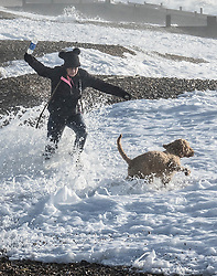 © Licensed to London News Pictures. 03/01/2018. Hayling Island, UK. A woman walking her dog gets caught out by a big wave as strong winds bring high tide on the beach at  Hayling Island as Storm Eleanor hits the south. Winds of up to 80 mph are being forecast today in parts of the UK. Photo credit: Peter Macdiarmid/LNP
