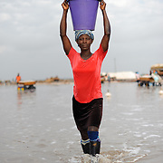 A woman carries a bucket of drinking water around a pan at the Ada Songor Salt project. Workers use a cup in the bucket to drink.
