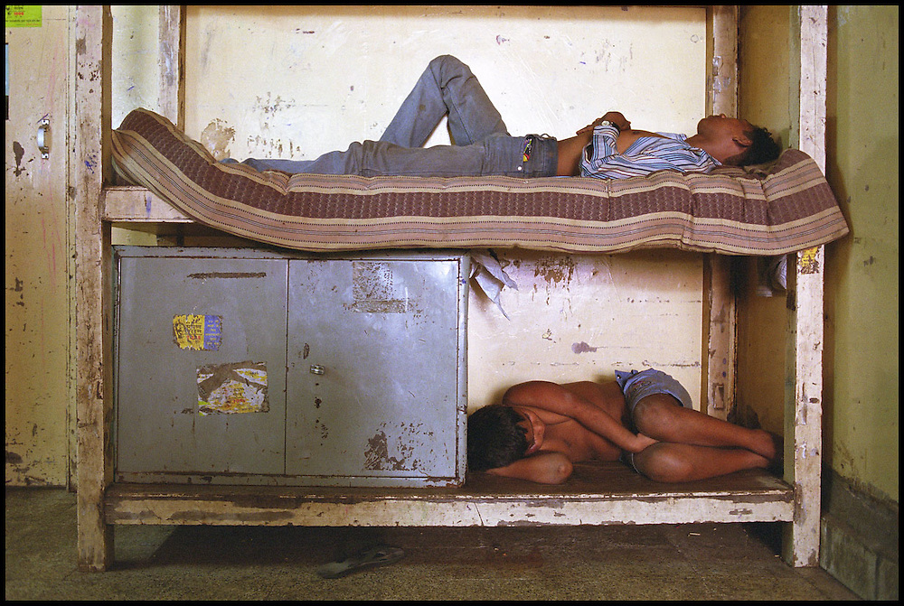 INDIA. Mumbai (Bombay). 2002. Adolescent and a younger handicapped (on the bottom) sleep in the shelter.