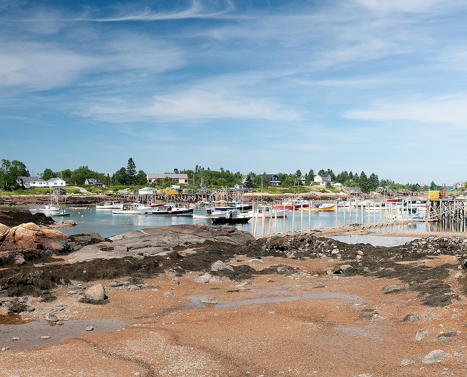 Schoodic Penninsula, Maine.  Late afternoon found me wandering the Maine Coast.  The little fishing village of Corea has long been a favorite of mine, and I hit it today at low tide.  The lobster boats were anchored for the day, surrounded by the exoskeleton of the harbor.  Not much stirred here, and it was strangely quiet at this hour, but for the random cries of the gulls.  Things don't change much in places like this, and much of it's beauty lies in the knowledge of it's steadfastness, it's successful history of life.  I get stares while I make my images...why do you find this so fascinating?  I am a stranger here.