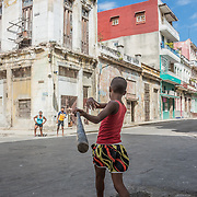 A boy hits a pop fly in a street baseball game in Havana, Cuba.
