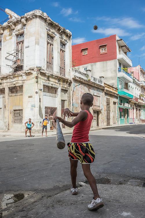 A boy hits a pop fly in a street baseball game in Havana, Cuba.