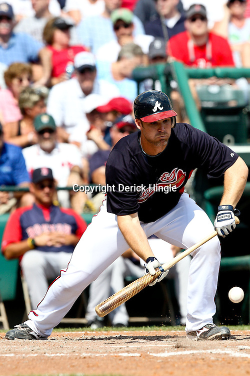 March 16, 2011; Lake Buena Vista, FL, USA; Atlanta Braves catcher David Ross (8) bunts for a one run single during a spring training exhibition game against the Boston Red Sox at the Disney Wide World of Sports complex.  Mandatory Credit: Derick E. Hingle