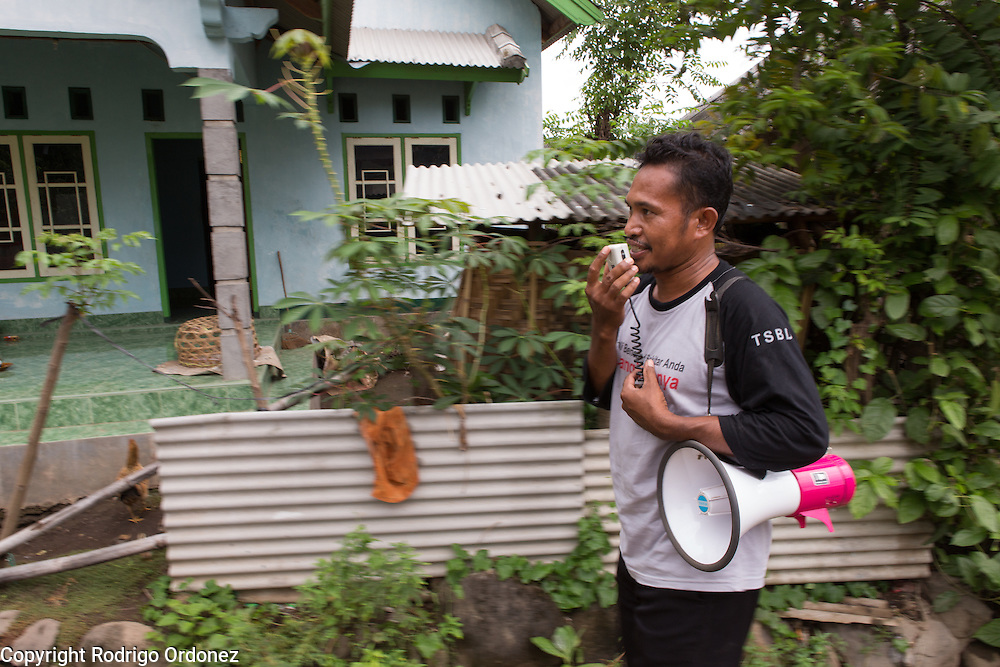 Muhuriadi, 42, a member of the emergency preparedness team in Belanting, performs an evacuation drill, using a megaphone to announce to villagers the need to evacuate. Belanting is located in Sambelia district, East Lombok, West Nusa Tenggara province, Indonesia.