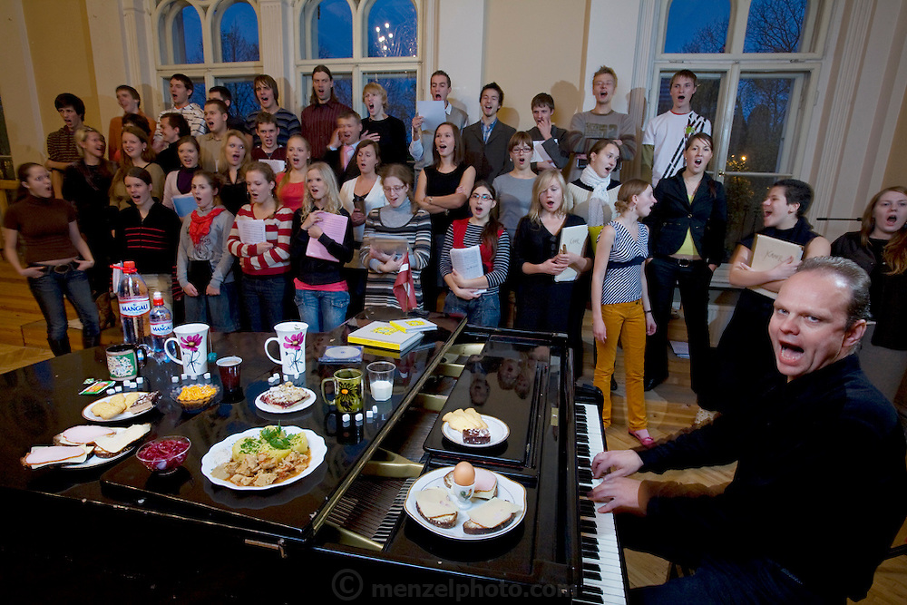 Ansis Sauka, a voice teacher, musician, and composer, with his typical day's worth of food while rehearsing the Riga youth choir Kamer in Riga, Latvia. (From the book What I Eat: Around the World in 80 Diets.) The caloric value of his typical day's worth of food on a day in the month of October was 3900 kcals. He is 36 years of age; 6 feet, 0,5 inches tall;  and 183 pounds. Riga, a UNESCO World Heritage Site with the oldest continuously running market in Europe, is known throughout Europe for its choral traditions. It proudly hosts the nationwide Latvian Song and Dance Festival every five years. In 2008 more than 38,000 singers, dancers, and musicians participated in the weeklong event. MODEL RELEASED.