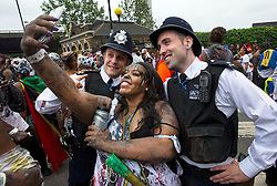 © Licensed to London News Pictures. 30/08/2015. London, UK. Two policemen pose for a selfie with a carnival goer at Family day at the Notting Hill Carnival in West London. The annual event, dating back to 1966, is one of the world's largest street festivals, attracting over one million people. Photo credit: Ben Cawthra/LNP