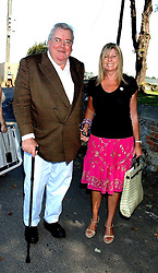 The HON.JOHN & MRS HESKETH at the wedding of musician Jools Holland to Lady Crystabel Durham held at Cooling Village Church, Cooling, Kent on 30th August 2005.<br />