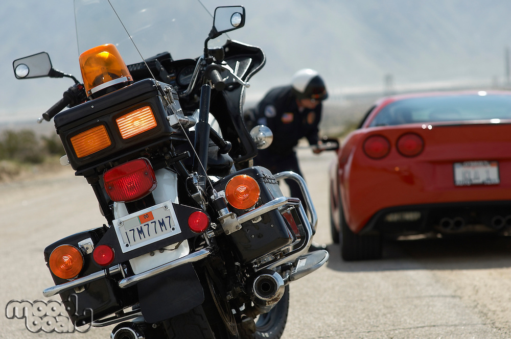 Traffic cop talking with sports car driver, focus on motorcycle in foreground