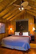 Guest bed in rustic luxury in cedar wood cabin, El Capitan Canyon Resort, near Santa Barbara, California