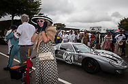 A woman dressed in vintage clothing covers her ears as engines roar at the paddock leading the the race course at the Goodwood Revival in Chichester, England   Friday, Sept. 9, 2016 The historic motor racing festival celebrates the mid-20th-century golden era of the racing circuit and recreates the atmosphere from the 1950s and 1960s.(Elizabeth Dalziel)