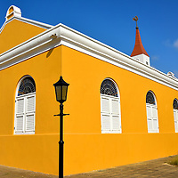 Protestant Church in Kralendijk, Bonaire<br /> This Protestant church was built on Wilhelmina Square in 1847 and the tower was added in 1868.  After spending a short time in Bonaire, you will notice numerous buildings are painted bright yellow. The Bonairean flag also has a yellow triangle in the upper left corner. This is an obvious reference to their bountiful sunshine.  However, the island also has two abundant trees that bloom with yellow flowers: the mesquite tree (also called palo de silla or brazil wood) and the kibrahacha.