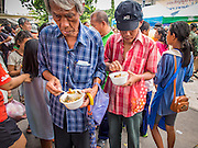 "07 AUGUST 2014 - BANGKOK, THAILAND: Men eat noodle soup provided by a Chinese foundation during a food distribution program at Pek Leng Keng Mangkorn Khiew Shrine in Bangkok. Thousands of people lined up for food distribution at the Pek Leng Keng Mangkorn Khiew Shrine in the Khlong Toei section of Bangkok Thursday. Khlong Toei is one of the poorest sections of Bangkok. The seventh month of the Chinese Lunar calendar is called ""Ghost Month"" during which ghosts and spirits, including those of the deceased ancestors, come out from the lower realm. It is common for Chinese people to make merit during the month by burning ""hell money"" and presenting food to the ghosts. At Chinese temples in Thailand, it is also customary to give food to the poorer people in the community.       PHOTO BY JACK KURTZ"